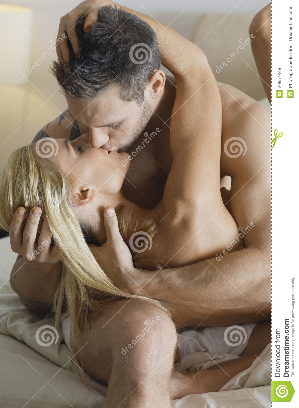 Naked passionate kissing in bed